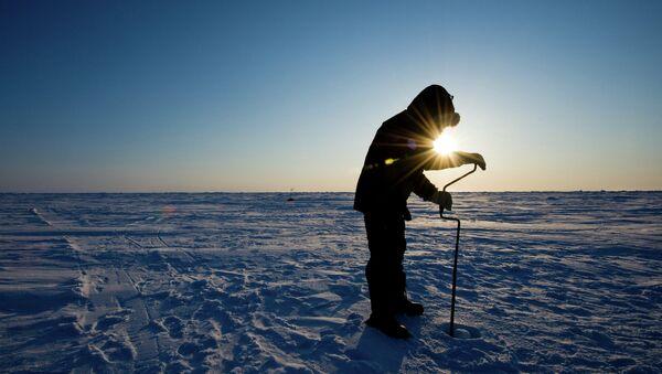 Российский ученый бурит лед для взятия пробы на Северном Полюсе. Архивное фото