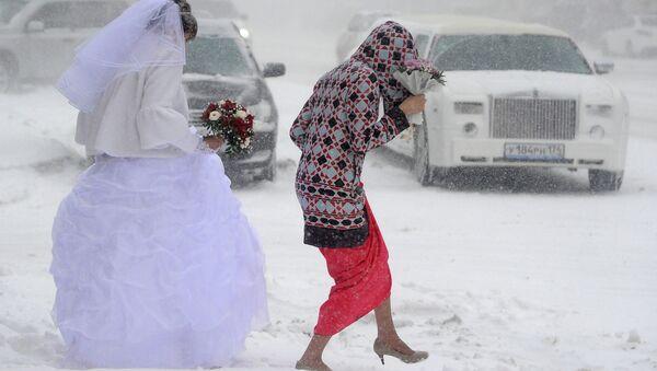МНевеста идет по улице во время сильного снегопада в Челябинске