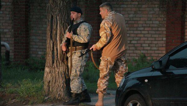 Бойцы сил самообороны сторонников федерализации на месте перестрелки у областного военкомата на улице города Луганска