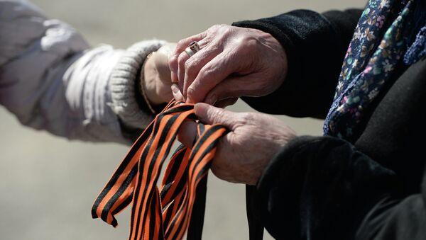 Волонтер раздает георгиевские ленточки