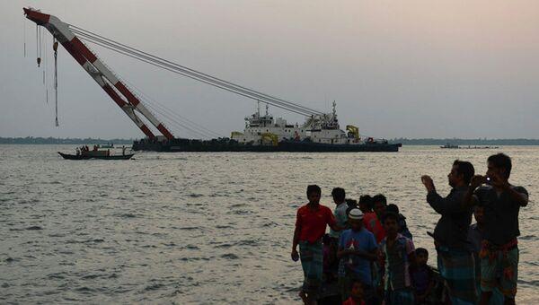 Бангладешские спасатели пытаются вытащить на берег затонувший паром