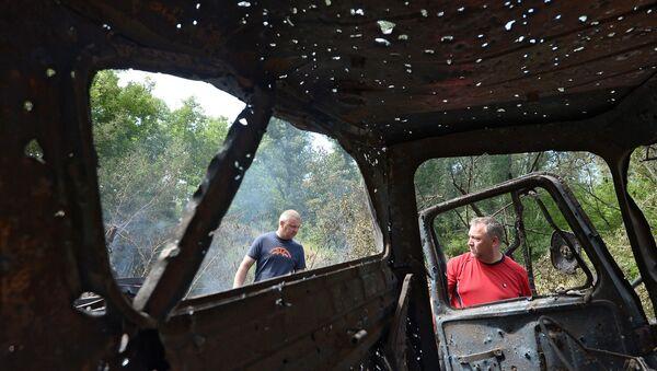 Жители города Рубежное осматривают обстрелянный и сгоревший автомобиль