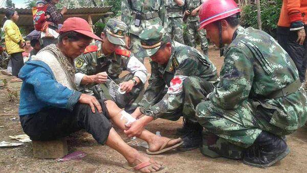 Военные оказывают помощь женщине, пострадавшей в результате землетрясения в Китае