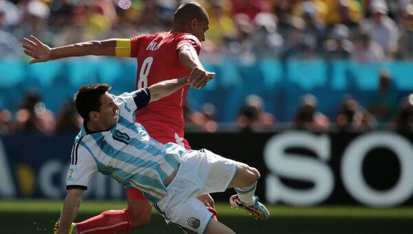 Игрок сборной Аргентины Лионель Месси (слева) и игрок сборной Швейцарии Гекхан Инлер в матче 1/8 финала чемпионата мира по футболу 2014 Аргентина - Швейцария на стадионе Арена Коринтианс в Сан-Паулу.