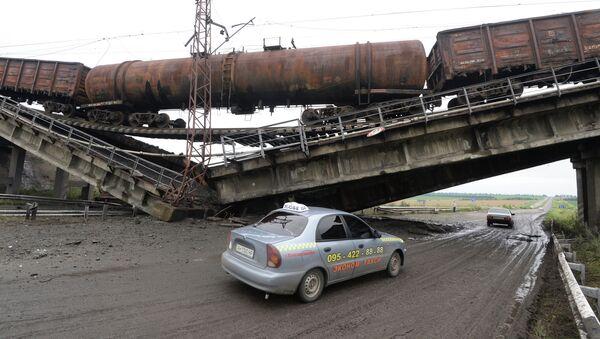 Автомобиль проезжает под взорванным железнодорожным мостом. Архивное фото