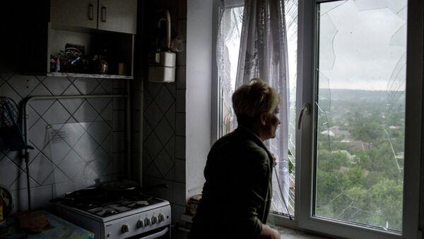 Женщина у окна с выбитыми стеклами в одной из квартир в пострадавшем от минометного обстрела украинскими силовиками жилом многоквартирном доме. Архивное фото