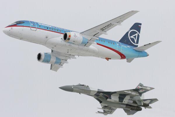Самолет Sukhoi SuperJet-100 (вверху) в сопровождении истребителя Су-35 (внизу)