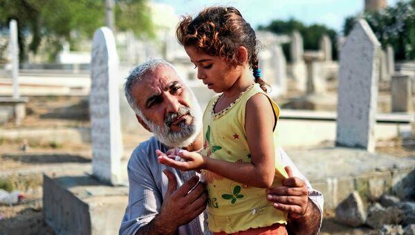 Мужчина с дочкой молятся возле могилы родственников в городе Газа