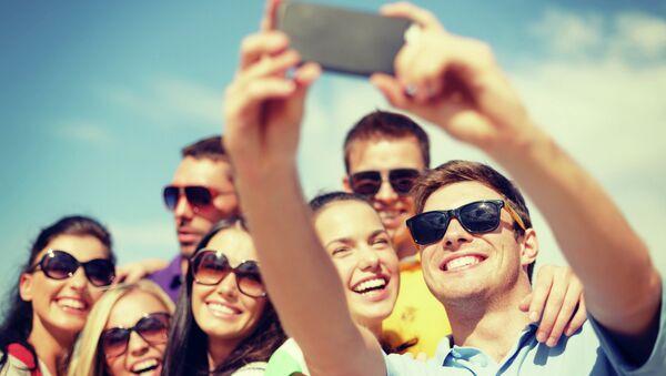Люди фотографируются на мобильный телефон