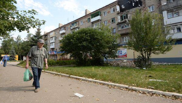 Мужчина идет возле поврежденного жилого дома в Горловке. Архивное фото