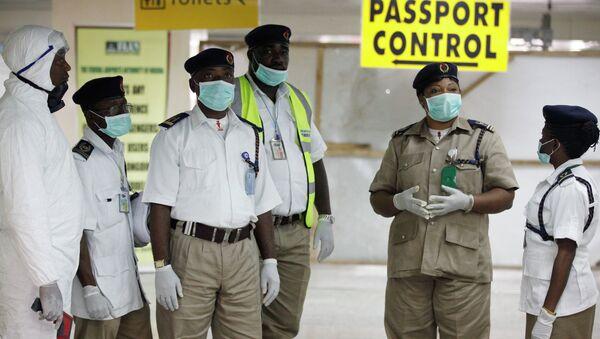 Сотрудники службы охраны здоровья ждут прибытия пассажиров в аэропорту Нигерии. Архивное фото