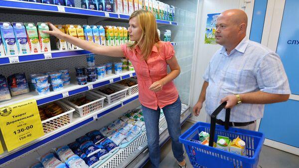 Покупатели у полки с молочной продукцией. Архивное фото