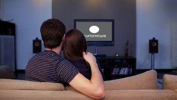 Девушка и молодой человек смотрят телевизор. Архивное фото
