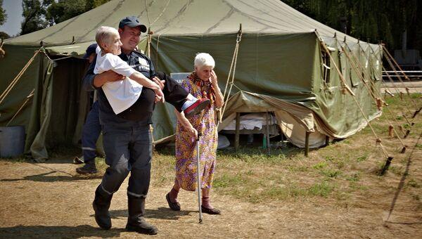 Сотрудник МЧС Украины переносит пожилую женщину, приехавшую из зоны силовой операции киевских властей на востоке Украины. Архивное фото