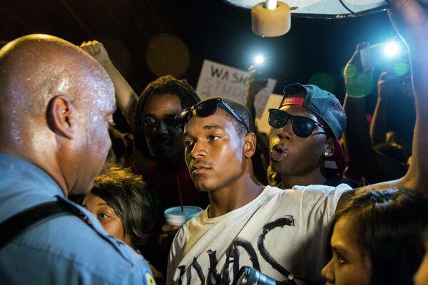 Полицейский Рон Джонсон общается с протестующими в пригороде Сент-Луиса, США