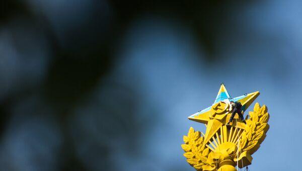 Рабочий закрашивает звезду на шпиле высотного здания на Котельнической набережной в Москве, которую выкрасили в голубой цвет.