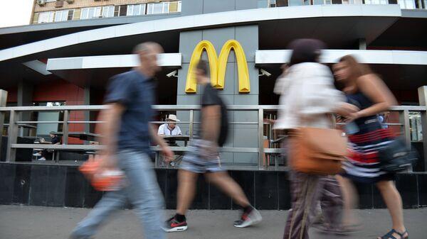 Люди проходят мимо закрытого ресторана быстрого питания Макдоналдс, архивное фото