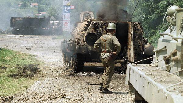 Солдат югославской армии стоит у машины после перестрелки с сотрудниками сил обороны Словении в Брежице, 1991 год