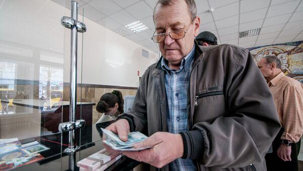 Мужчина получает пенсию в почтовом отделении. Архивное фото