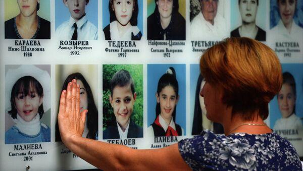 Женщина на траурном мероприятии в годовщину трагедии в Беслане