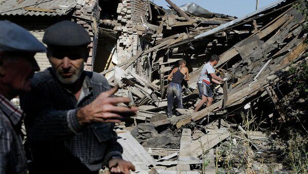 Местные жители разбирают завалы на месте жилого дома пострадавшего в результате боев под Иловайском