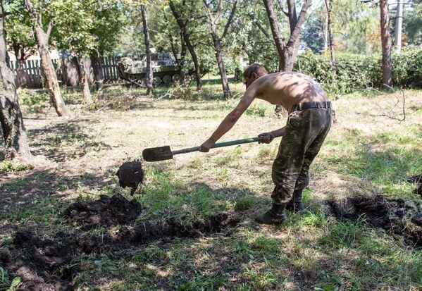 Пленный украинский военный роет могилу для погибших сослуживцев в результате боев в городе Шахтерск под Донецком