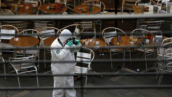 Полицейский делает снимки на месте взрыва рядом со станцией в Сантьяго, Чили