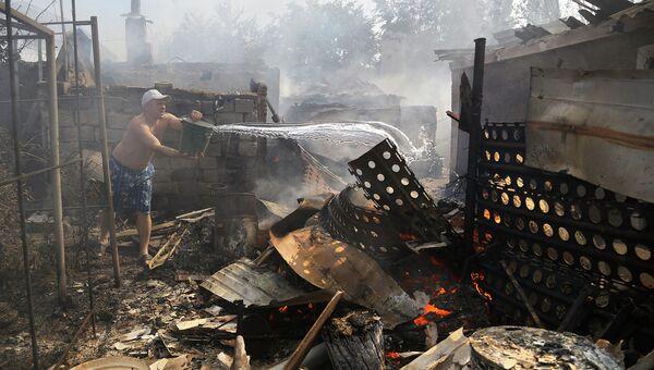 Житель Донецка тушит пожар в своем доме после обстрела. Архивное фото