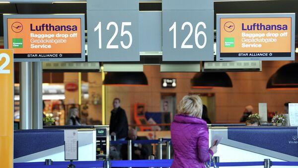 Пассажирка стоит у стойки регистрации авиакомпании Lufthansa. Архивное фото