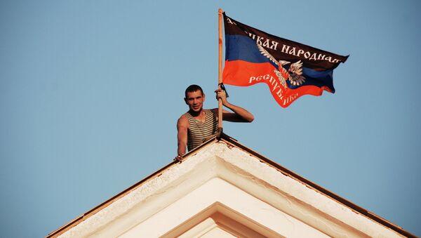 Ополченец устанавливает флаг ДНР на здании мэрии города Комсомольское Донецкой области. Архивное фото