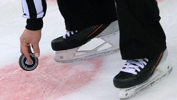 Судья держит шайбу перед вбрасыванием в матче регулярного чемпионата КХЛ