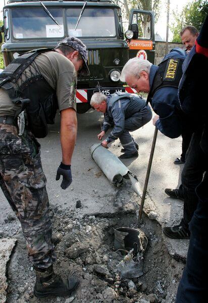 Спасатели и ополченцы достают из земли осколки снаряда после обстрела Донецка
