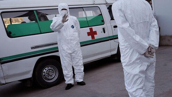 Медицинские сотрудники одетые в защитные костюмы в международном аэропорту Сунан в Пхеньяне. Архивное фото