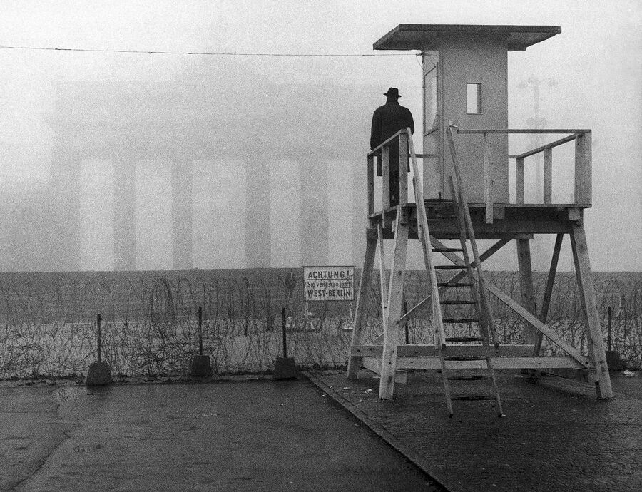 Человек смотрит на Бранденбургские ворота, расположенные на восточной стороне Берлинской стены