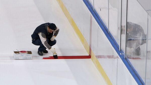 Строитель наносит разметку на лед хоккейного катка. Архивное фото
