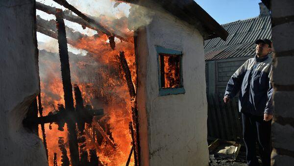 Житель Донецка у своего дома, разрушенного и горящего после артиллерийского обстрела