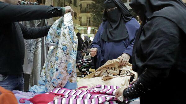Женщины выбирают одежду на рынке