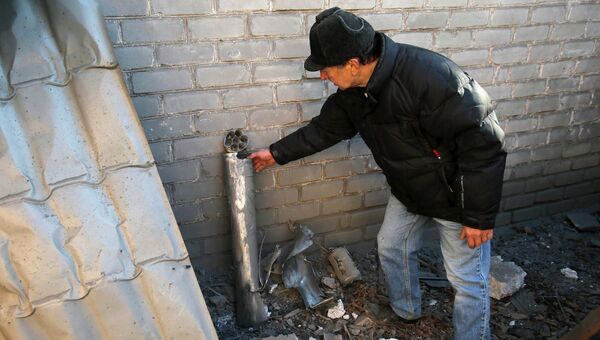 Мужчина показывает обломки снаряда после обстрела его дома в Донецке