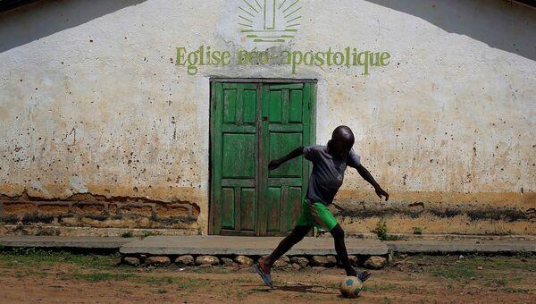 Ребенок с мячом в сельской местности Гвинеи. Архивное фото