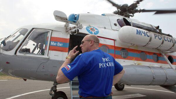 Сотрудник МЧС у вертолета, архивное фото