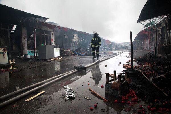 Пожарный идет мимо сожженных павильонов в центре Грозного.