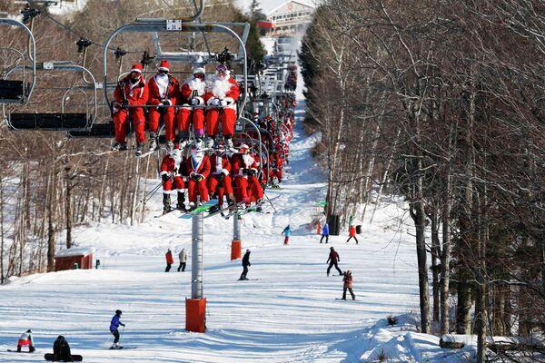 Люди в костюмах Санта-Клауса перед началом благотворительного забега по горнолыжному склону в штате Мэн, США