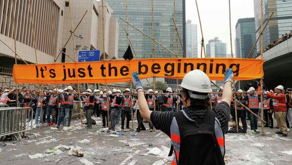 Рабочие демонтируют баннер, установленный протестующими в Гонконге