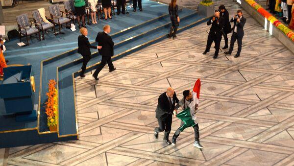 Сотрудник службы безопасности уводит молодого человека с мексиканским флагом во время церемонии награждения Нобелевской премии мира. Осло, 10 декабря 2014 год