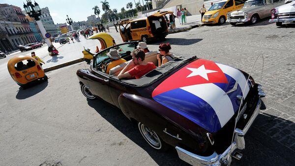 Туристы катаются на классическом американском кабриолете с кубинским национальным флагом в Гаване