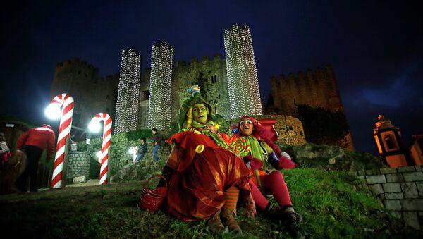 Женщины, переодетые эльфами, во время рождественского представления возле замка Обидуш, Португалия