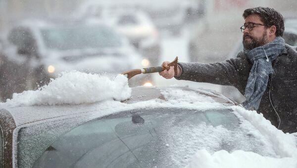 Автовладелец счищает снег с автомобиля в Москве