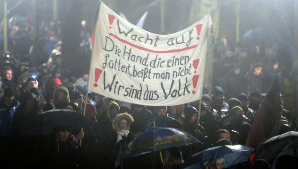 Участники акции протеста в Германии, выступающие против нетерпимости в отношении иммигрантов и движения Pegida