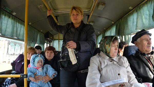 Кондуктор и пассажиры рейсового автобуса. Архивное фото