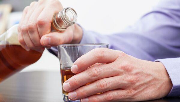 Мужчина держит бутылку с крепким алкоголем